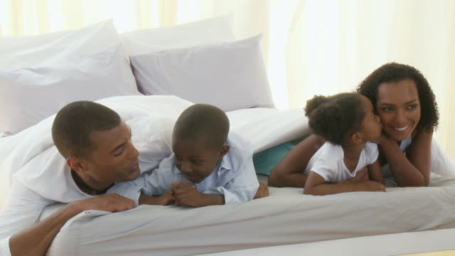 MS Parents with son and daughter (4-5) lying under sheets in bed / Cape Town, Western Cape, South Africa
