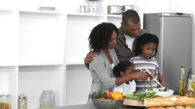 MS PAN Parents with son (8-9) and daughter (4-5) mixing salad in kitchen / Cape Town, Western Cape, South Africa