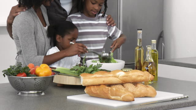 MS TU Parents with son (8-9) and daughter (4-5) mixing salad in kitchen / Cape Town, Western Cape, South Africa