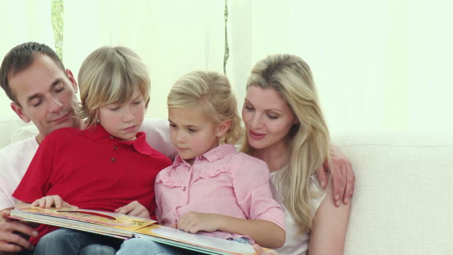ms pan parents with son and daughter (8-9) reading book together on sofa / cape town, south africa - see other clips from this shoot 1811 stock videos & royalty-free footage