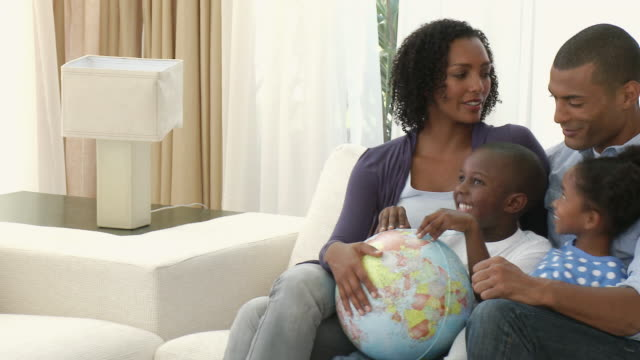 stockvideo's en b-roll-footage met ms pan parents with son and daughter (4-5) sitting on sofa and looking at globe together / cape town, western cape, south africa - bureauglobe