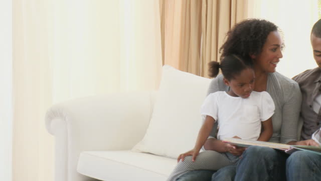 vidéos et rushes de ms pan parents with son (8-9) and daughter (4-5) sitting on sofa and reading book together / cape town, western cape, south africa - prendre sur les genoux