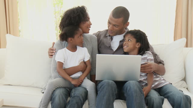 MS Parents with son (8-9) and daughter (4-5) sitting on sofa and using laptop together / Cape Town, Western Cape, South Africa