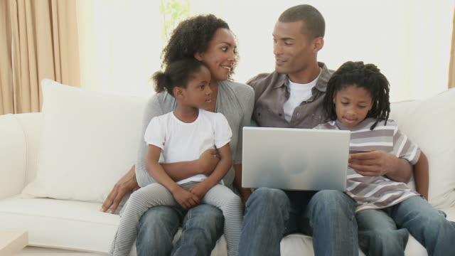 MS PAN Parents with son (8-9) and daughter (4-5) sitting on sofa and using laptop together / Cape Town, Western Cape, South Africa