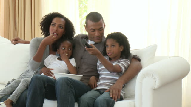 MS PAN Parents with son (8-9) and daughter (4-5) sitting on sofa and watching television together / Cape Town, Western Cape, South Africa