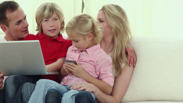 ms pan parents with son and daughter (8-9) sitting on sofa using laptop / cape town, south africa - see other clips from this shoot 1811 stock videos & royalty-free footage
