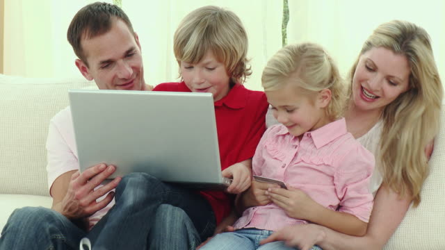 ms parents with son and daughter (8-9) sitting on sofa using laptop / cape town, south africa - see other clips from this shoot 1811 stock videos & royalty-free footage