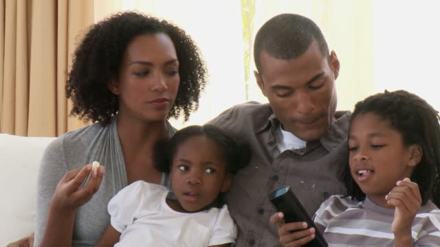 CU Parents with son (8-9) and daughter (4-5) watching television together / Cape Town, Western Cape, South Africa