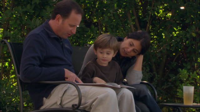CU, ZO, MS, Parents with son (4-5) reading book in garden, Los Angeles, California, USA