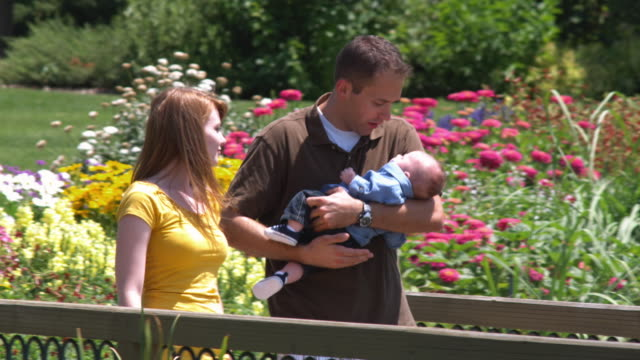 SLO MO MS PAN Parents with son (2-5 months) walking in park / Utah, USA