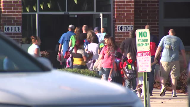 parents with their children at the first day of school during the coronavirus pandemic in baker county, florida. - healthcare and medicine or illness or food and drink or fitness or exercise or wellbeing stock videos & royalty-free footage