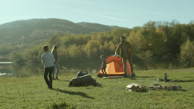 Parents with their sons playing frisbee and badminton on camping trip by the lake