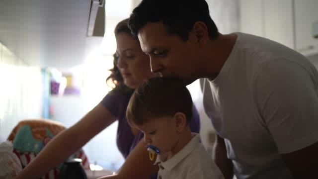 vídeos y material grabado en eventos de stock de padres con niño pequeño a la hora del desayuno en casa - familia con un hijo