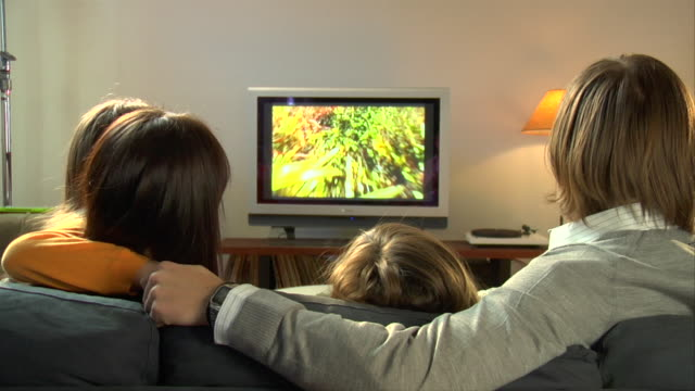 vidéos et rushes de cu, parents with two children (8-9, 10-11) sitting on sofa, watching television, rear view - living room