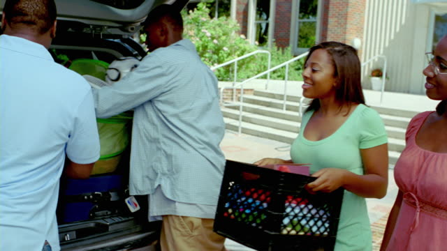 ms, swish  pan, parents with two teenage children (18-19) unloading belongings from car trunk outside college dorm building, san antonio, texas, usa, swish pan - swish pan stock videos & royalty-free footage