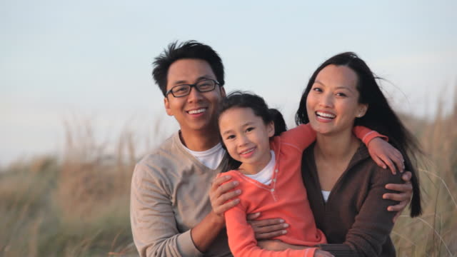 ms pan parents with young daughter sitting together on beach dunes / eastville, virginia, usa - eastville stock videos and b-roll footage