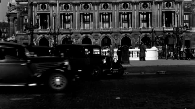 dx - paris - 1938-1939 era - ground level toward the opera house - heavy traffic - many black and white taxi-cabs - traffic, policemen f.g. - b&w. - 1938 stock videos & royalty-free footage