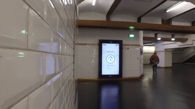 vidéos et rushes de paris, april 20, 2020. metro corridors with only one person, warning sign regarding covidus. metro in paris, during the confinement of coronavirus. - panneau commercial