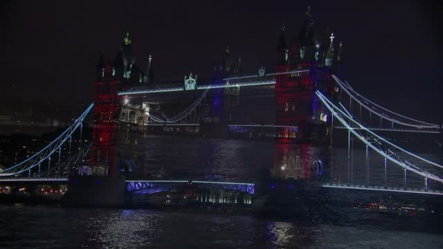British response Downing Street French tricolor on flagpole above Downing Street Tower Bridge illuminated in red white and blue Millennium Wheel lit...