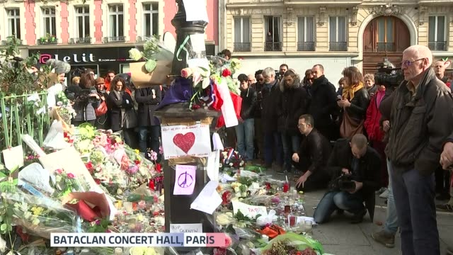 minute's silence observed across europe crowds stand for minutes silence around floral tributes outside bataclan theatre / crowds stand in place de... - mass murder stock videos & royalty-free footage