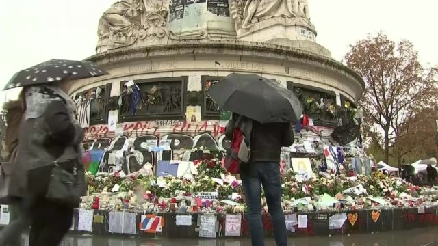 vidéos et rushes de survivor interview france paris woman looking at flowers on monument at the place de la republique bv people looking at flowers and tributes int... - mémorial
