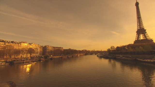 Paris Golden sunrise Camera pans across the Seine River golden sun reflects on the river and surrounding buildings Sun just over horizon silhouettes...