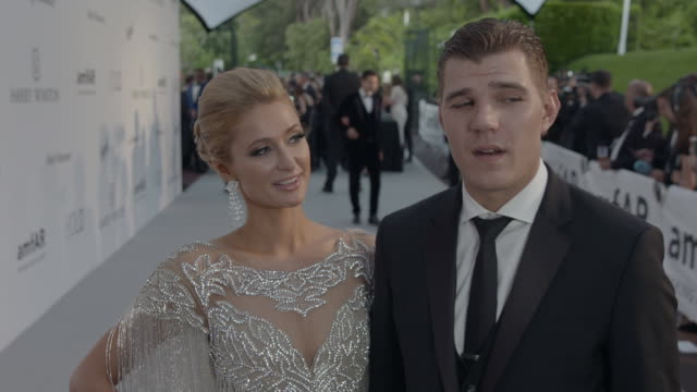 INTERVIEW Paris Hilton Chris Zylka on being at amfAR on the performances on the party on the auction at amfAR Gala Cannes 2017 at Hotel du CapEdenRoc...