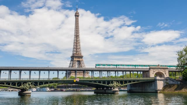 paris metro crossing seine river on pont de bir-hakeim with eiffel tower in background - fiume senna video stock e b–roll