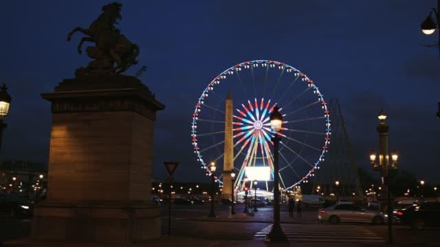 Paris Place de la Concorde and its ferris wheel at night with car passing by