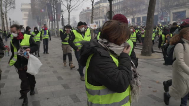 vídeos de stock, filmes e b-roll de paris protests yellow vest movement protesters in street marching and affected by tear gas - vest