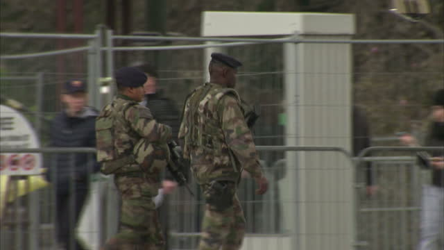 vidéos et rushes de paris reaction to belgium terror attacks showing exterior shots armed soldiers walking through crowd increased security in streets of paris on march... - armement