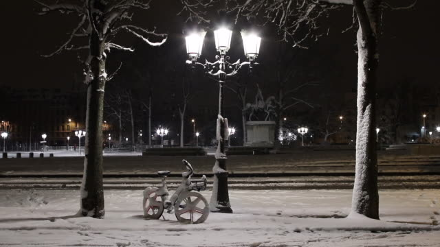 Paris with snow at night, 2018, bike under a lamppost