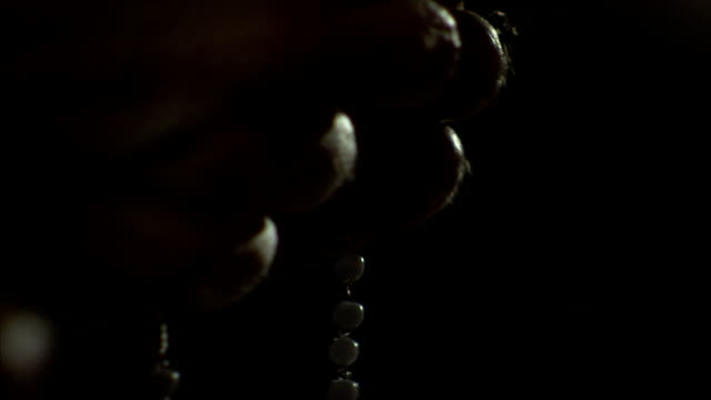 a parishioner counts beads on a rosary. available in hd. - rosary beads stock videos & royalty-free footage