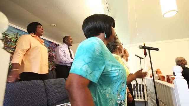 parishioners sing during sunday services in the rebuilt christian community baptist church in the lower ninth ward on may 10, 2015 in new orleans,... - バプテスト点の映像素材/bロール