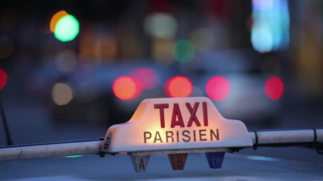 cu pan selective focus parisian taxi light and traffic on street at dusk, paris, france - taxi stock videos & royalty-free footage