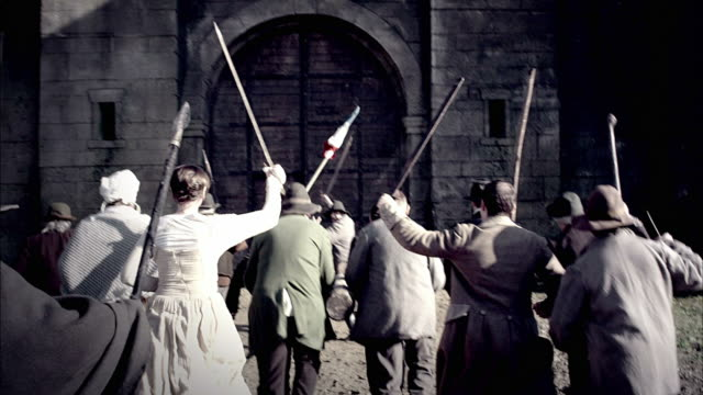 parisian villagers use farm implements as weapons to destroy the bastille. - rivoluzione francese video stock e b–roll
