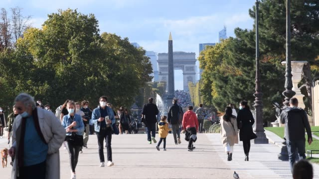 parisians enjoy the sun in the tuileries gardens on october 21 in paris france about 20 million french people are covered by the monthlong curfew in... - arc de triomphe paris stock videos & royalty-free footage