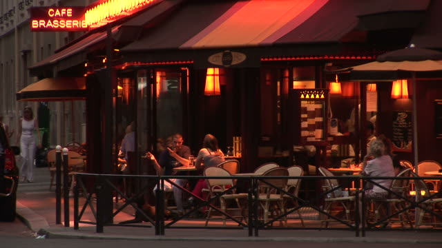 parisview of a coffee shop at magic hour in paris france - cafe stock videos & royalty-free footage