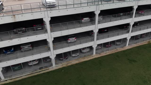 vídeos y material grabado en eventos de stock de park and drive multi story parking lot aerial side view - piso de edificio