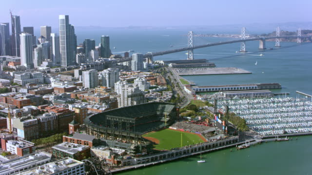 aerial at&t park by the san francisco waterfront and the bay bridge in the background on a sunny day - san francisco bay bridge stock videos and b-roll footage