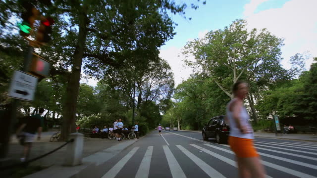 ws pov park filled with joggers, cyclists, pedestrians / new york city, new york, usa - road signal stock videos & royalty-free footage
