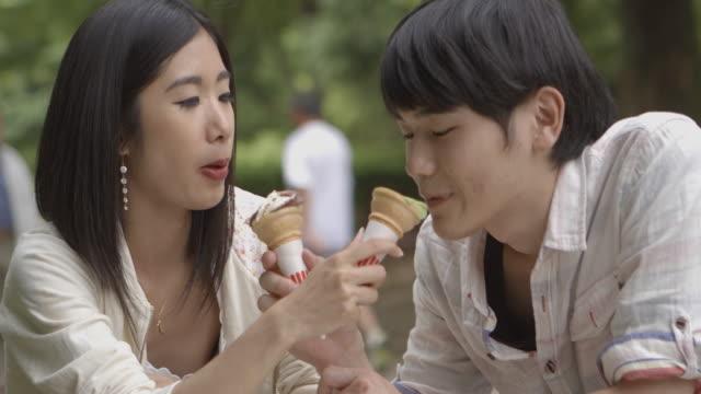 公園日本の若いカップルの読書本東京。 - アイスクリーム点の映像素材/bロール