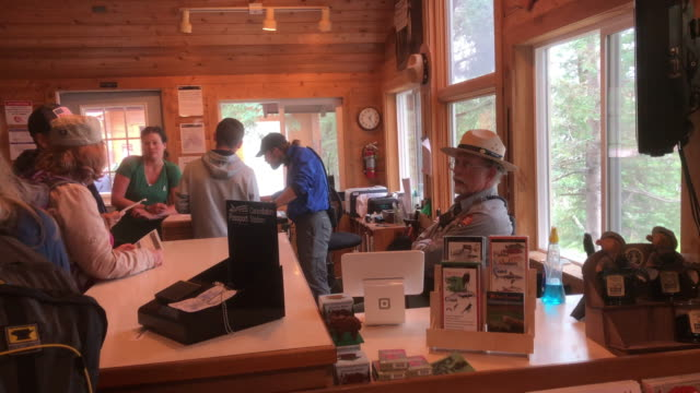 park ranger talking to tourists on camping check in at the katmai national park visitor center, alaska. - 公園保安官点の映像素材/bロール