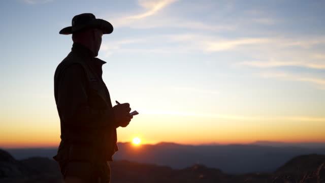 日没時に紙に書き込むパークレンジャー - 公園保安官点の映像素材/bロール