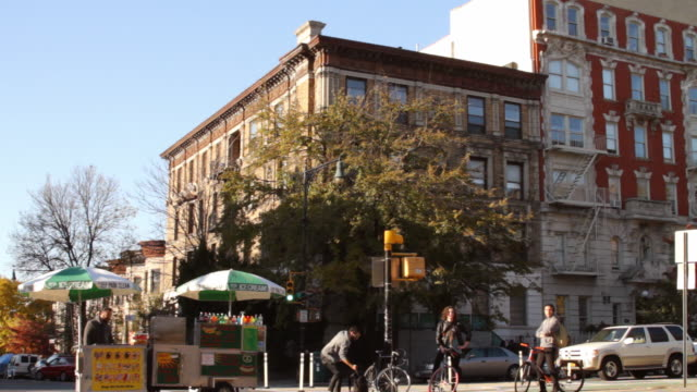 a park slope, brooklyn street scene with a hotdog vendor and cyclists - bancarella video stock e b–roll
