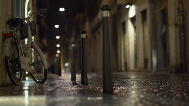 a parked bicycle under the rain at night in verona - senza persone video stock e b–roll