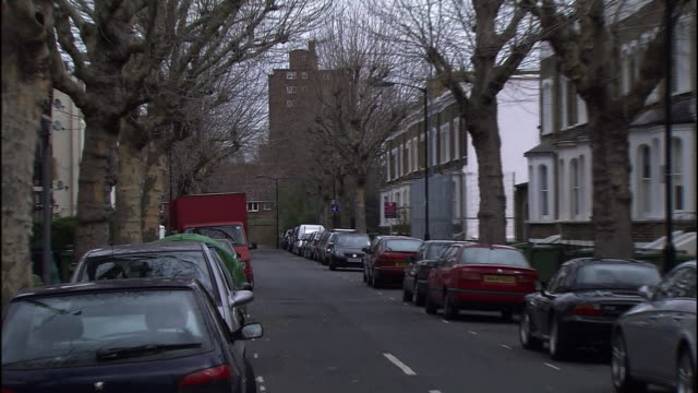 Parked cars and apartment buildings line a residential street in London.