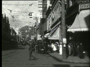 vidéos et rushes de b/w parked cars and people on honolulu street / 1919 / no sound - 1910 1919