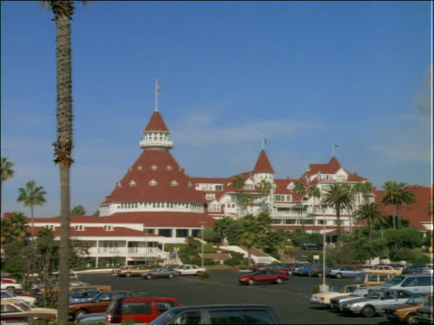 parked cars in front of hotel del coronado / zoom in to hotel / san diego - 2001 stock-videos und b-roll-filmmaterial