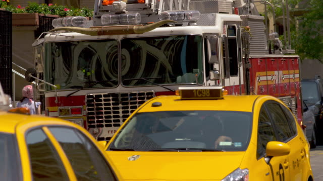 a parked fire truck sits idle on the side of the street.  the fire truck has cow horns on top. - stationary stock videos and b-roll footage